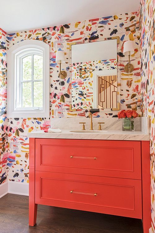 A bright colourful bathroom with wallpaper and coral vanity